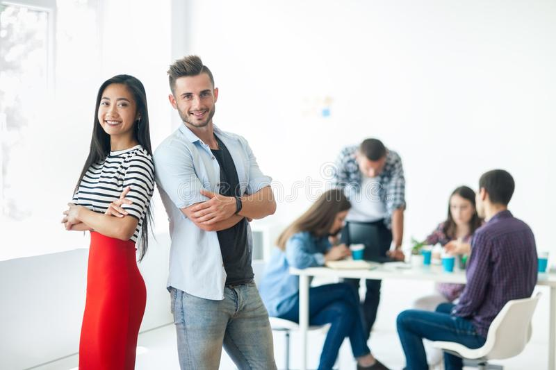 Smiling businessman and businesswoman standing back to back stock photography