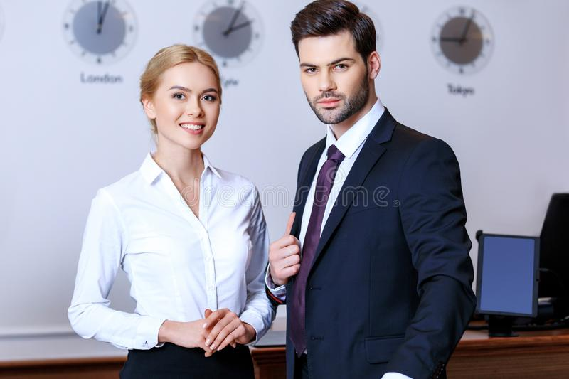 Smiling businessman and businesswoman standing at reception desk. In hotel royalty free stock photos