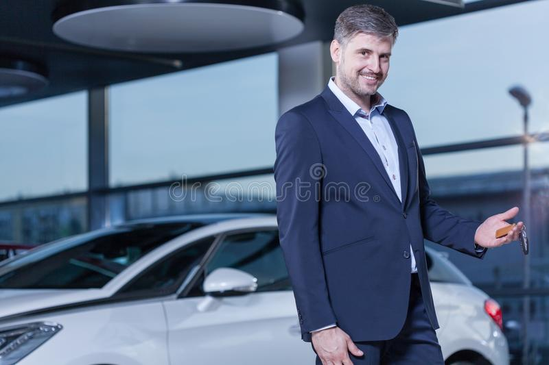 Smiling businessman buying car. Photo of smiling young businessman buying new car royalty free stock photography