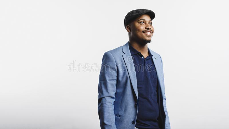 Smiling businessman in cap. Smiling african american man standing against white background. Man wearing a suit and cap looking away royalty free stock images