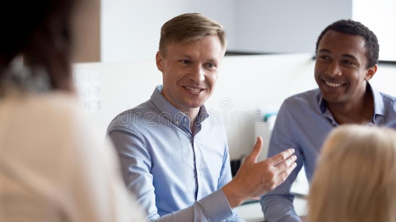 Smiling businessman coach speaking to diverse colleagues employees at meeting royalty free stock photography