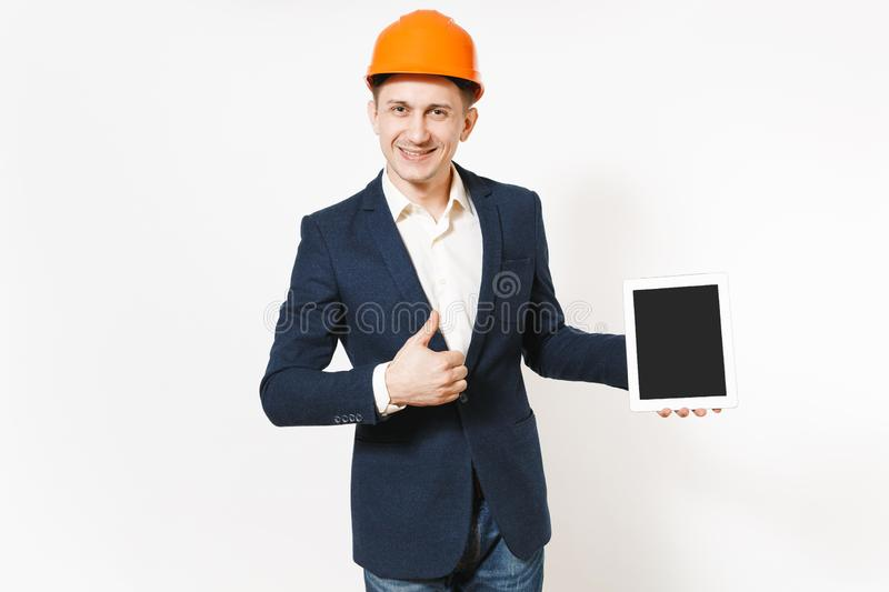 Smiling businessman in dark suit, protective hardhat holding tablet pc computer with blank screen and showing thumb up stock photo