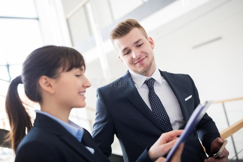 Businessman Discussing With Colleague Over Clipboard royalty free stock images