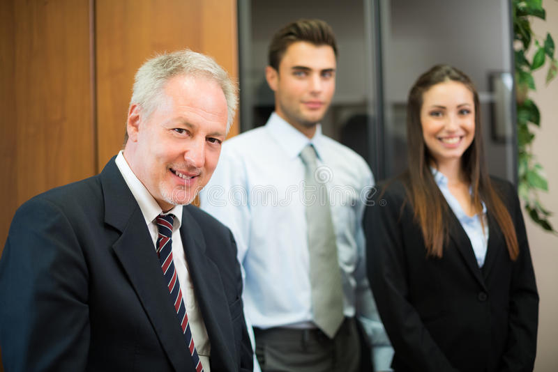 Smiling businessman in front of his colleagues royalty free stock photo