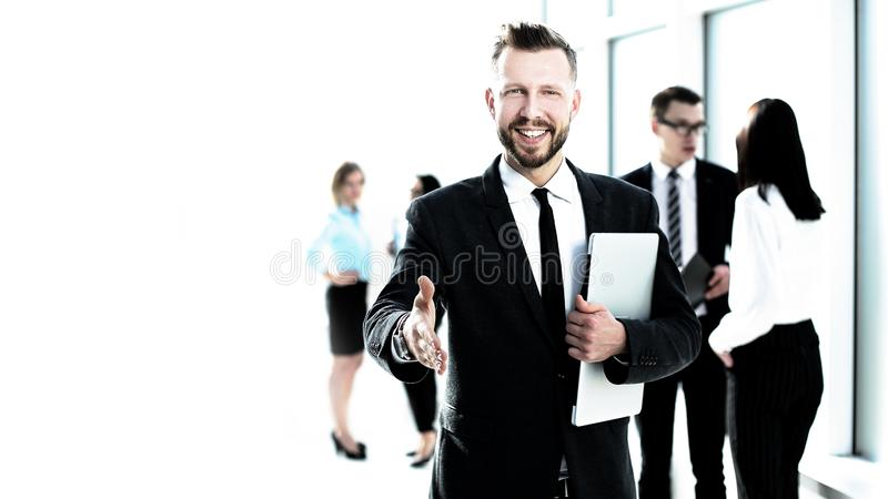Smiling businessman giving his hand for a handshake stock photos