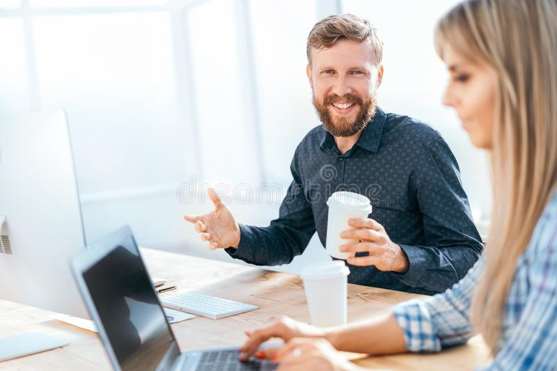 Smiling businessman with a glass of coffee sitting at his Desk royalty free stock photography