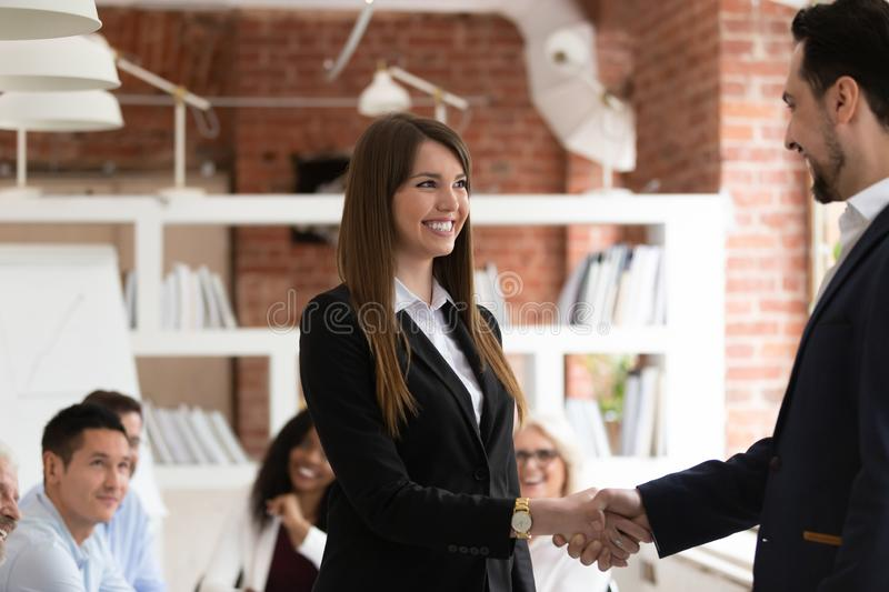 Smiling businesspeople handshake congratulating with success at meeting. Smiling businessman handshake excited female employee congratulating with personal stock photography