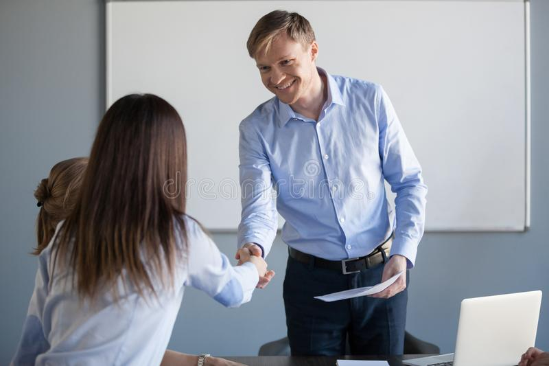 Smiling businessman handshake female worker greeting with promot. Smiling male boss shaking hand of female employee, congratulating with good work results at royalty free stock image