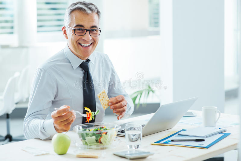 Smiling businessman having a lunch break royalty free stock photos