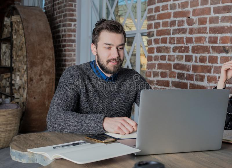 Young bearded hipster guy skilled freelancer working on laptop computer, sitting in co-working space. stock images