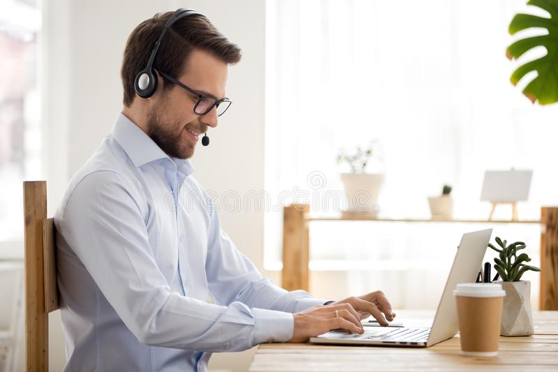 Smiling businessman in headset working on laptop make conference videocall. Smiling businessman in headset working on laptop make conference video call using stock images