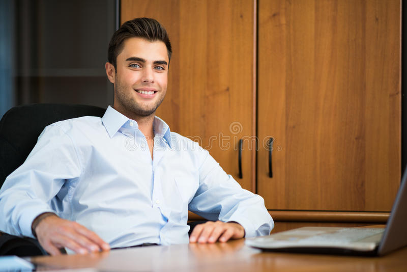 Smiling businessman in his office stock images