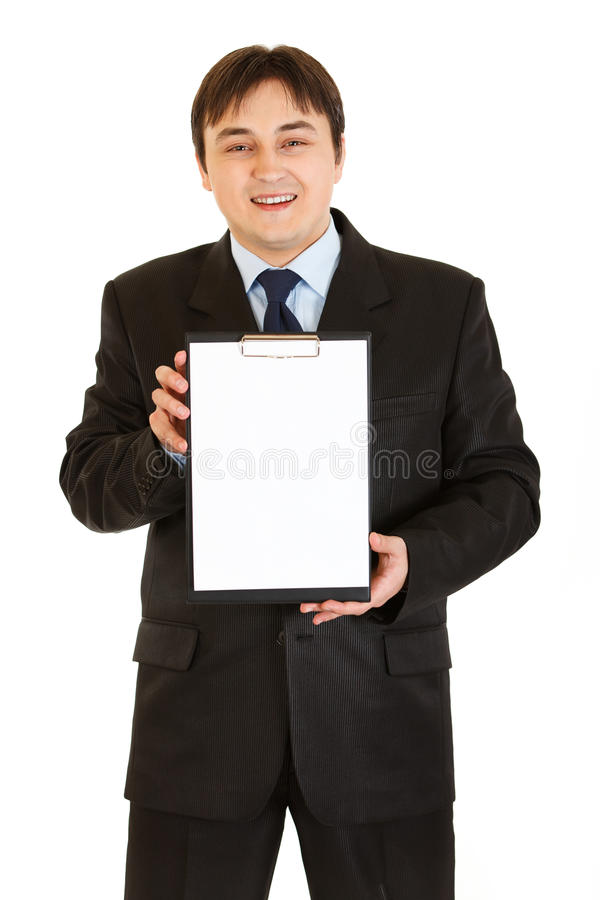 Smiling businessman holding blank clipboard royalty free stock photography
