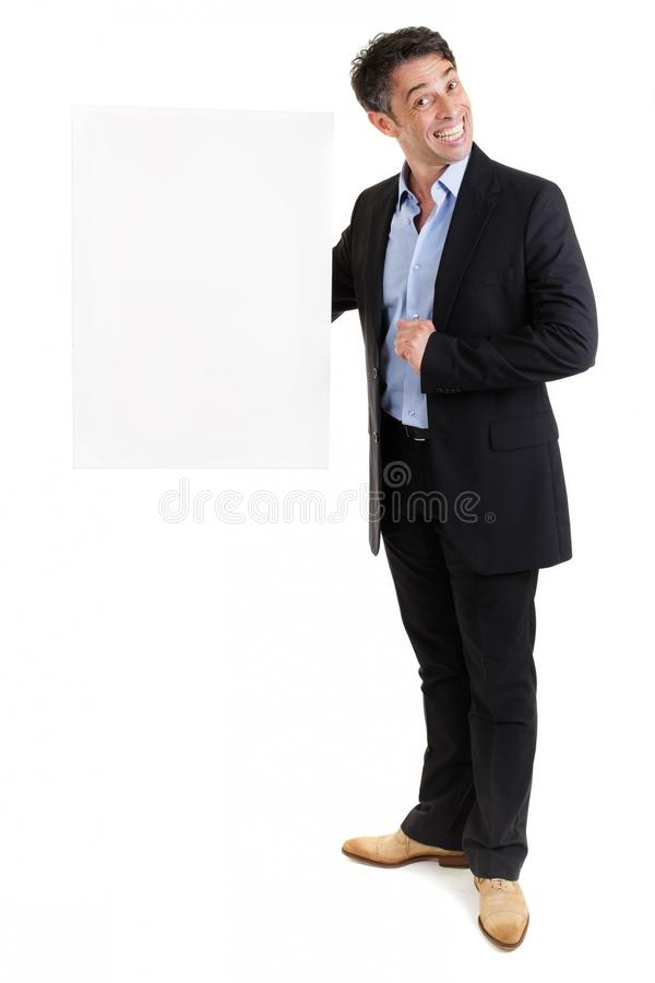 Smiling businessman holding a blank. Fun portrait of a smiling businessman with a wide toothy grin holding a blank white sign in his hand with copyspace as he stock photography