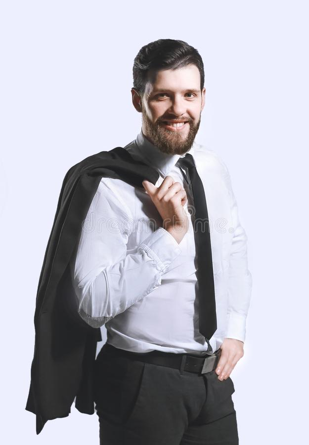 Smiling businessman holding a jacket over his shoulder and straightens the tie stock images
