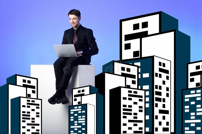 Smiling businessman with laptop sitting on white block between drawing buildings. On blue royalty free stock image