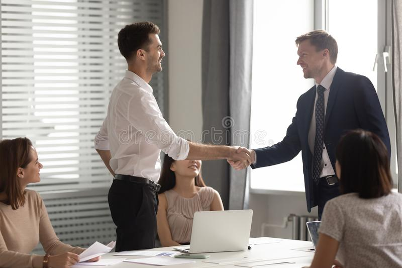 Smiling businessman leader shaking hand of employee at meeting royalty free stock photos