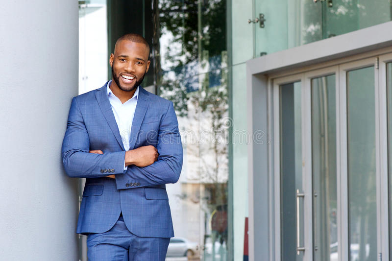 Smiling businessman leaning against wall outdoors. Portrait of smiling businessman leaning against wall outdoors with his arms crossed stock photos