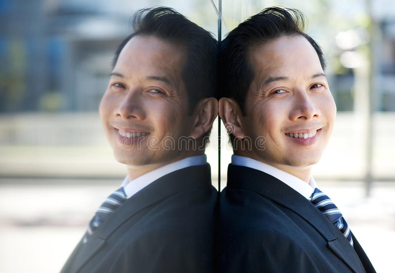 Smiling businessman leaning on wall royalty free stock photography