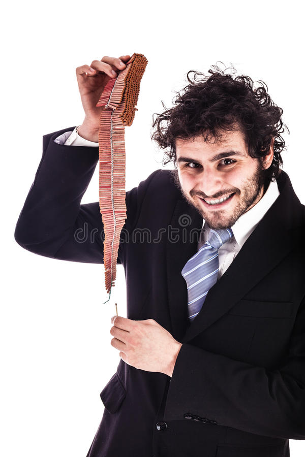 Smiling businessman lighting chained firecrackers stock image