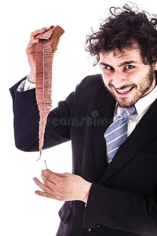 Smiling businessman lighting firecrackers royalty free stock image