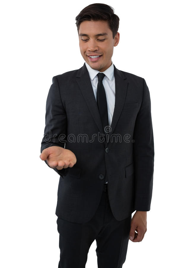 Smiling businessman looking at palm of hand. While standing against white background royalty free stock photos