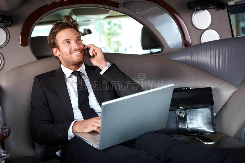 Smiling businessman in luxury car working royalty free stock images