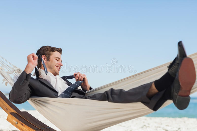 Smiling businessman lying in hamock taking off his tie. At beach royalty free stock photo
