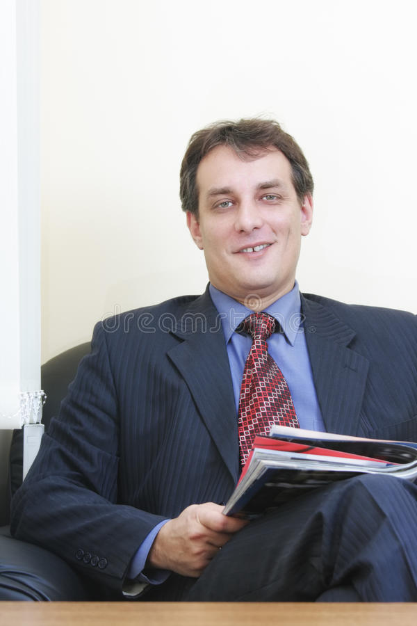 Download Smiling Businessman With Magazine Stock Photo - Image: 12715238
