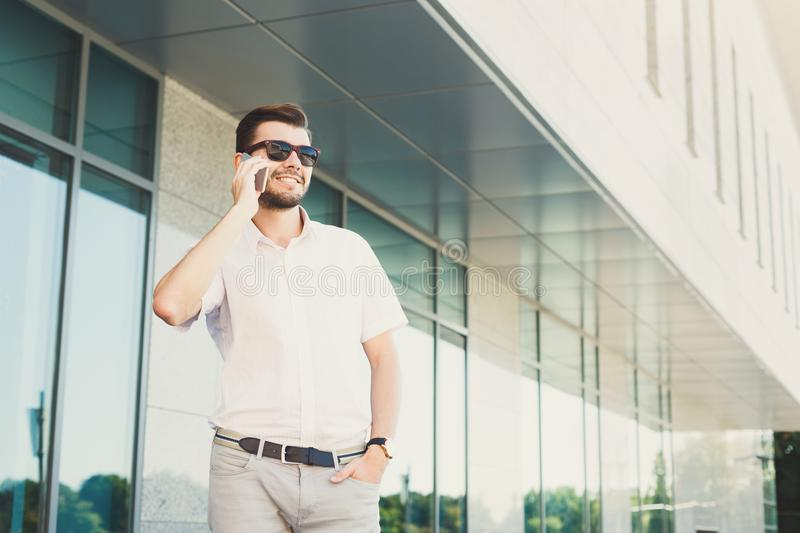 Smiling businessman making a phone call outdoors royalty free stock photography