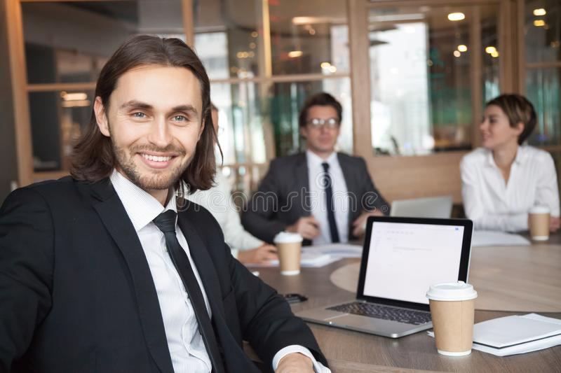 Smiling businessman manager in suit looking at camera at meeting royalty free stock photo