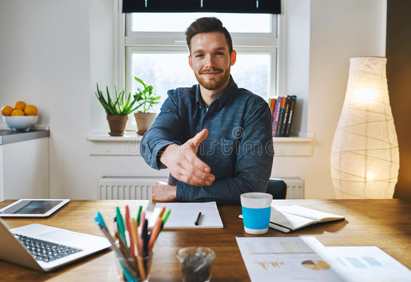 Smiling businessman offering his hand. Smiling businessman leaning across his desk offering his hand in greeting, to close a deal, in partnership or royalty free stock photo
