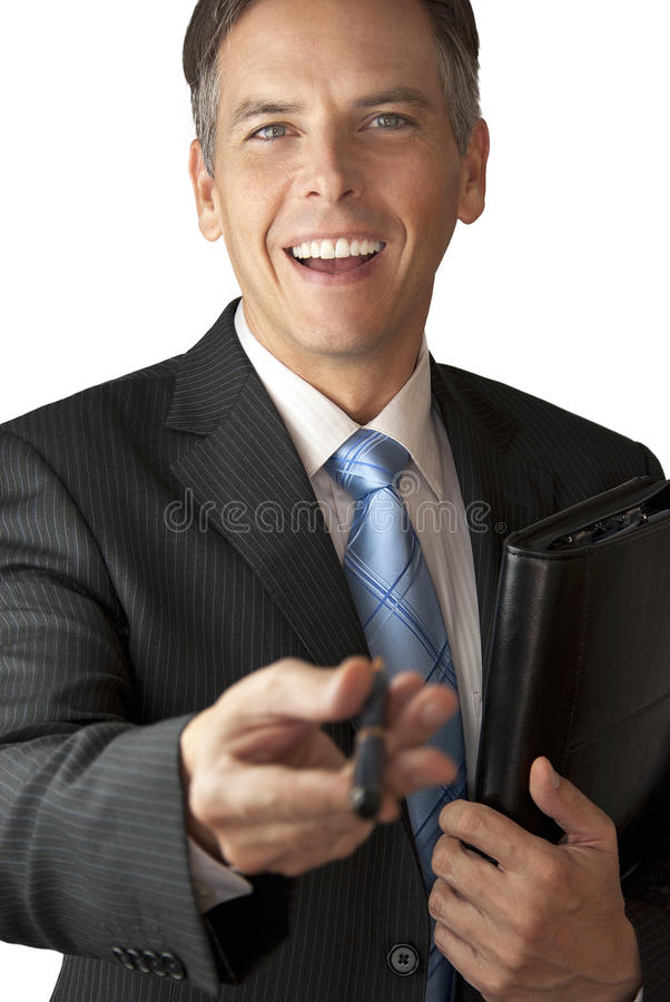 Smiling Businessman Offers Pen With Leather Portfo. A full frame shot of a smiling confident businessman offering his pen to camera with a leather portfolio stock image