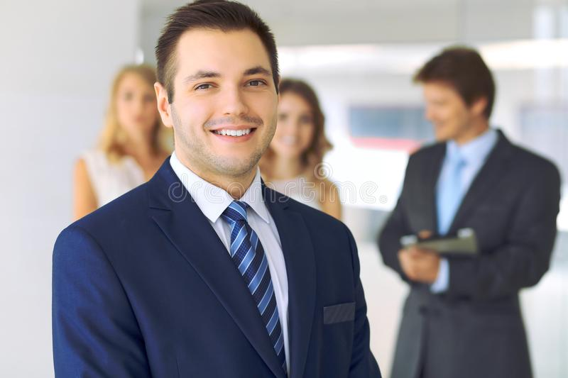 Smiling businessman in office with colleagues in the background royalty free stock photography