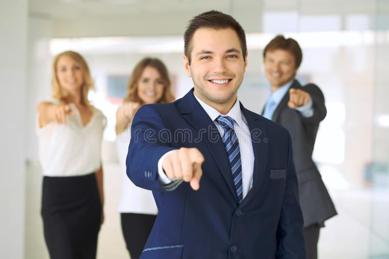 Smiling businessman in office with colleagues in the background. Pointing by finger into the camera royalty free stock images