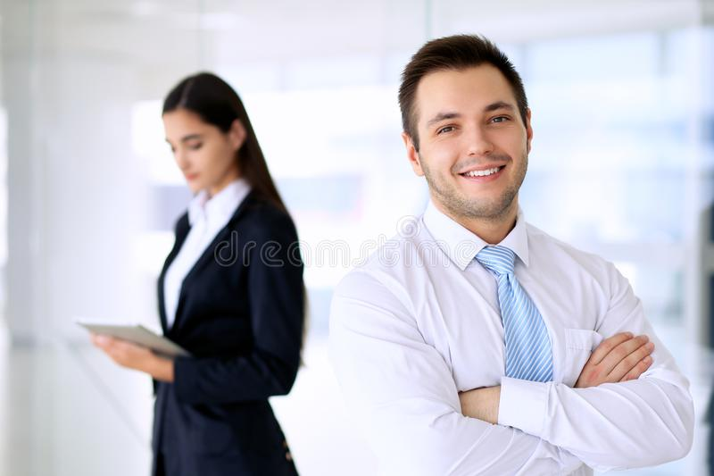 Smiling businessman in office with colleagues in the background royalty free stock photo