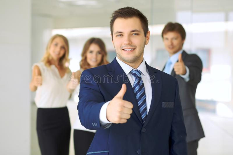 Smiling businessman in office with colleagues in the background. Thumbs up royalty free stock photography