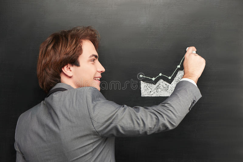 Smiling businessman painting graph on chalkboard stock image