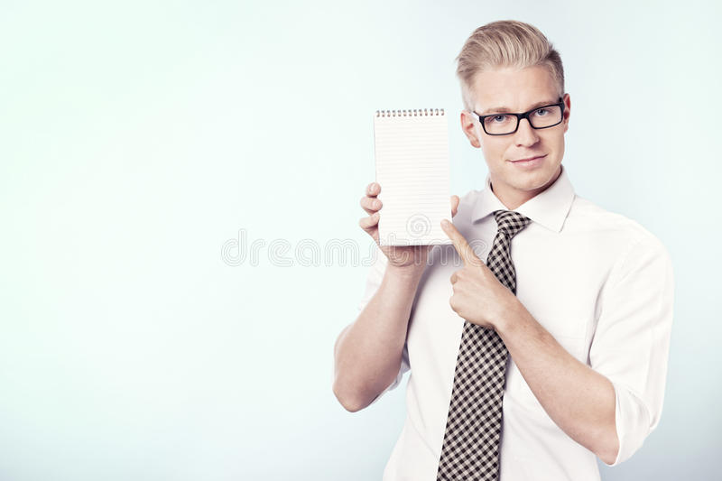 Smiling businessman pointing finger at blank notebook. Friendly young businessman pointing finger at empty notepad with space for text, isolated stock image