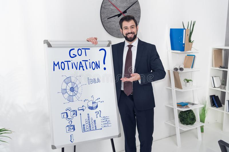 smiling businessman pointing at whiteboard with got motivation inscription and business graphs royalty free stock photo