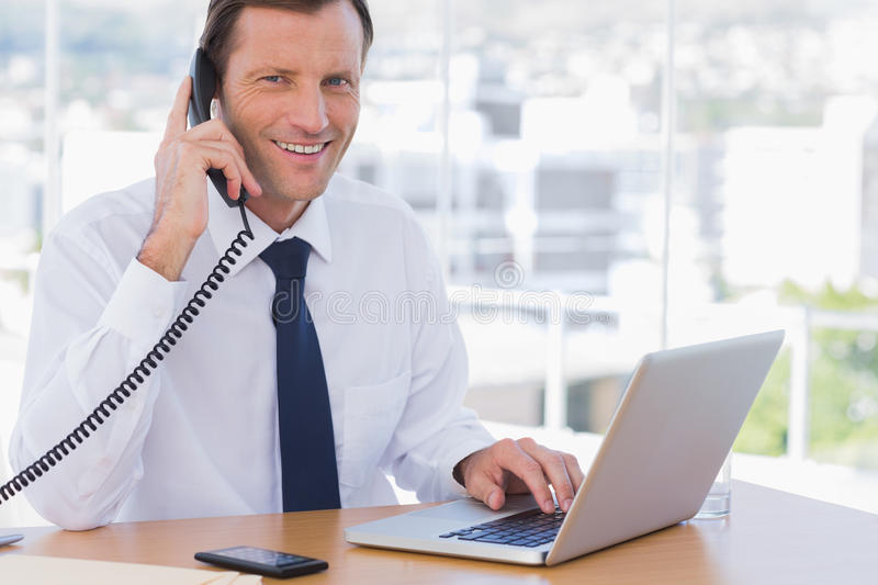 Smiling businessman posing while he is on the phone royalty free stock photography