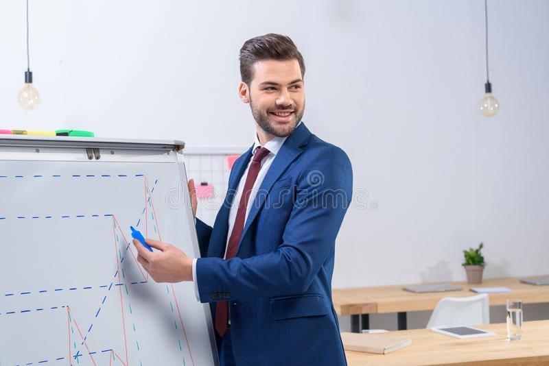 Smiling businessman presenting diagram chart. At meeting stock photography