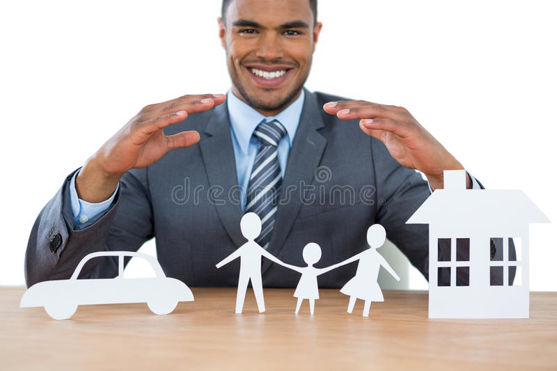 Smiling businessman protecting paper cut out family, house and car with hands. Portrait of smiling businessman protecting paper cut out family, house and car stock photos