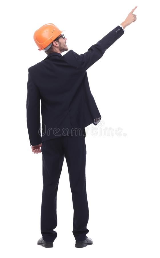 Smiling businessman in a protective helmet pointing at copy space. In full growth. smiling businessman in a protective helmet pointing at copy space. isolated on royalty free stock photos