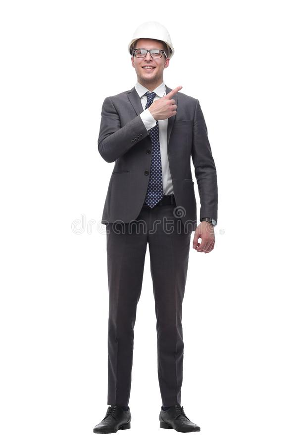 Smiling businessman in a protective helmet pointing somewhere to the side stock photography