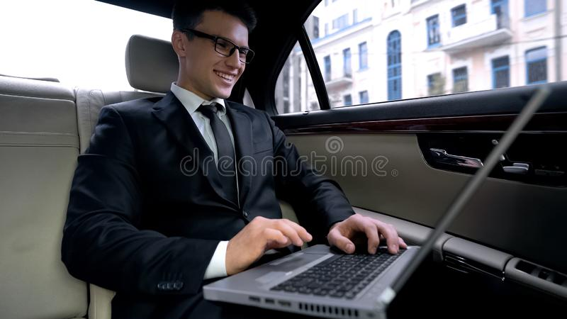 Smiling businessman reading good news on laptop, riding in car, workaholic stock image