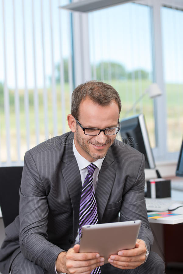 Smiling Businessman Reading His Tablet-pc Stock Photos