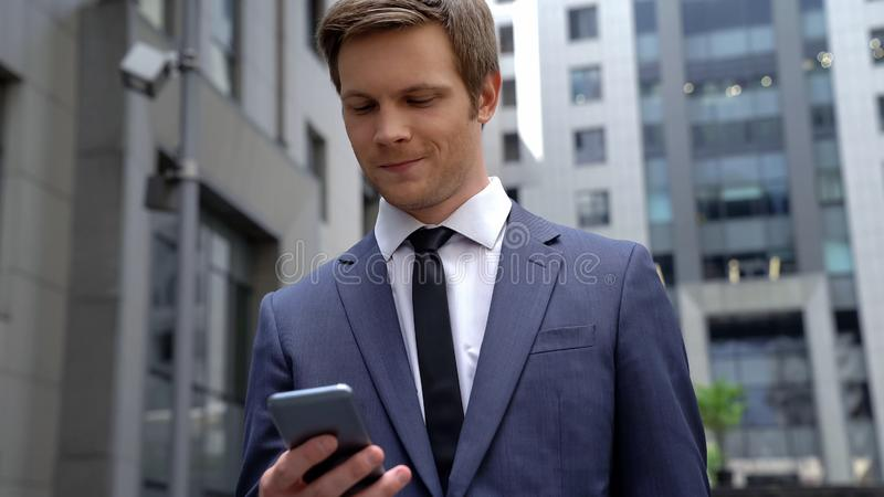 Smiling businessman reading message on smartphone successful investment, startup royalty free stock images