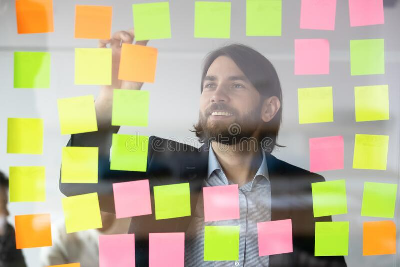 Smiling businessman reading tasks on sticky papers, post it notes royalty free stock photo