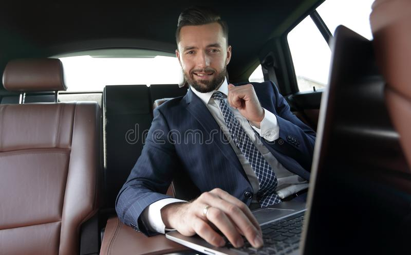Businessman reads information on laptop while sitting in car royalty free stock photography